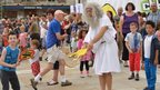 Spectators watch as toga-clad man plays rubber chicken tennis