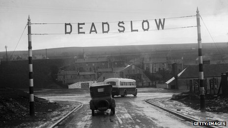 "A ""dead slow"" sign on a road c. 1930"