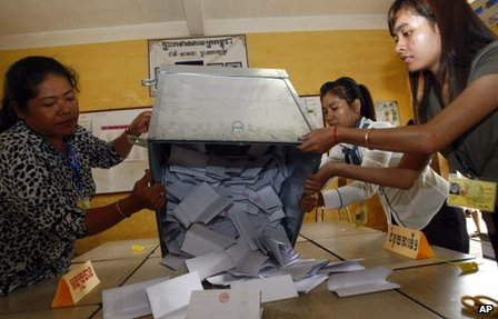 Officials open a ballot box for counting