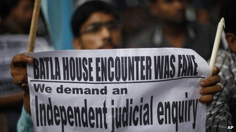 A protester holds a placard during a protest march against the recent judgement in Batla House encounter case in Delhi on 27 July 2013