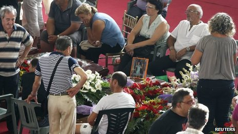 People mourn next to the coffins of victims of a coach crash before the start of the funeral service at the Monteruscello Palasport near Pozzuoli July 30, 2013.