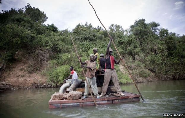 A team of Senegalese men punting a raft carrying a generator for use at a banana plantation