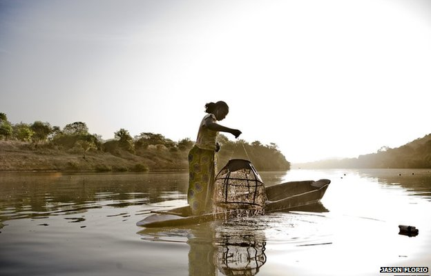 A female migrant worker from Mali pulls up fishing pots