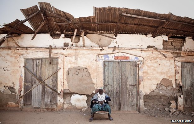 A village elder relaxes outside an abandoned colonialwarehouse in Kuntuar village