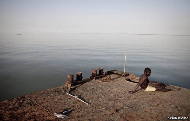 A watchman relaxes on a  jetty near the samll Gambian village of Bonto