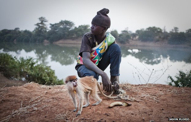 Musa Jallow with his pet Patas monkey who he rescued after hunters killed its mother