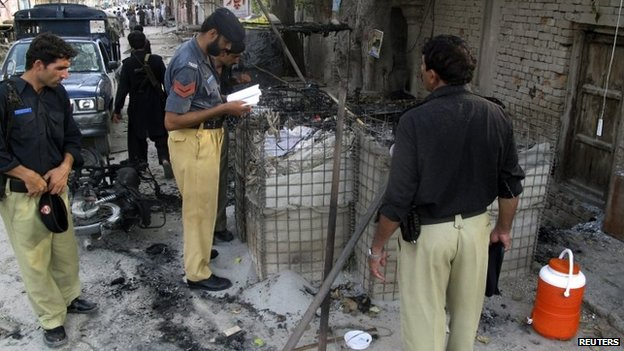 Policemen collect evidence outside the Dera Ismail Khan prison on Tuesday