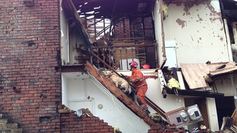 A firefighter and dog search the partially collapsed property