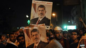 Supporters of Mohammed Morsi hold up posters in Cairo (30 July 2013)