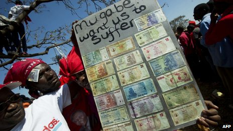 Supporters of Zimbabwe's Prime Minister Morgan Tsvangirai hold a sign with different Zimbabwean dollar bills ranging in value from Z$5 to Z$500m