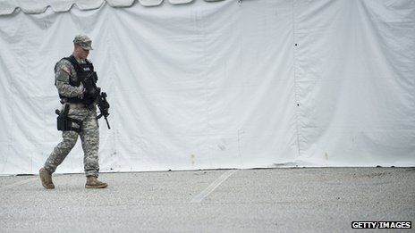 An armed man patrols the grounds near the military trial