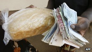 A Zimbabwean purchases bread in Harare on 21 September 2008 with the Zimbabwe dollar equivalent of $2
