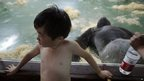 A boy cools off as a gorilla lies sprawled inside an air conditioned room at a zoo in Shanghai, China, 26 July 2013