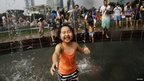 A girl participates in a water fight at People's Square in Shanghai, 21 July 2013