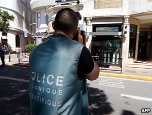 A police photographer takes pictures of the store robbed in Cannes, 31 July