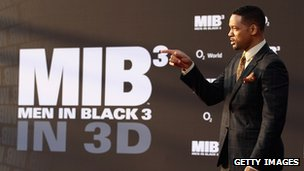Actor Will Smith in front of a Men in Black 3 poster