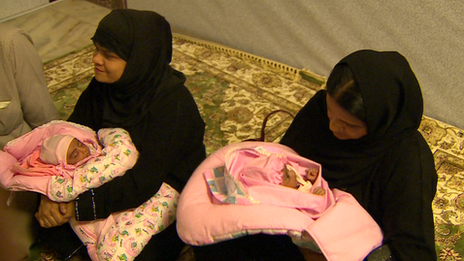 Two women clad in chadors holding babies