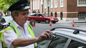 Traffic warden photographing car