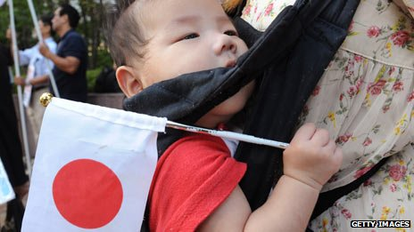 Baby clinging to its mother while holding a Japanese flag