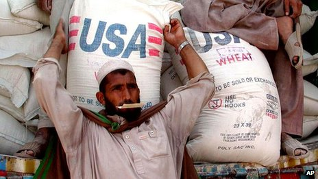 A man unloads wheat at a refugee camp in Pakistan