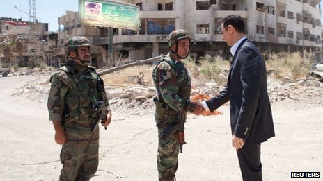 Syrian President Bashar al-Assad greets soldiers in Daraya, outside Damascus, on Thursday in an image released by state news agency Sana