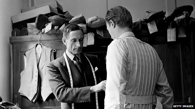 Leonard Barratt takes the measurements of a customer to be fitted with a bulletproof waistcoat in Pall Mall, London