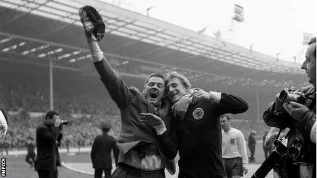 An ecstatic Scotland fan celebrates with Denis Law at the final whistle