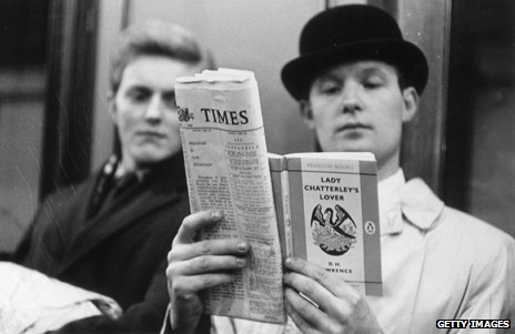A man in a bowler hat circa 1960 reading Lady Chatterley's Lover on a train as another passenger looks over his shoulder