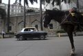 A Premier Padmini taxi rides past a horse drawn carriage in Mumbai