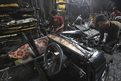 Indian workers dismantle a Mumbai Premier Padmini taxi in a scrap yard, in Mumbai