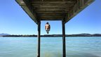 A woman jumps into the water of Lake Forggen in southern Germany.