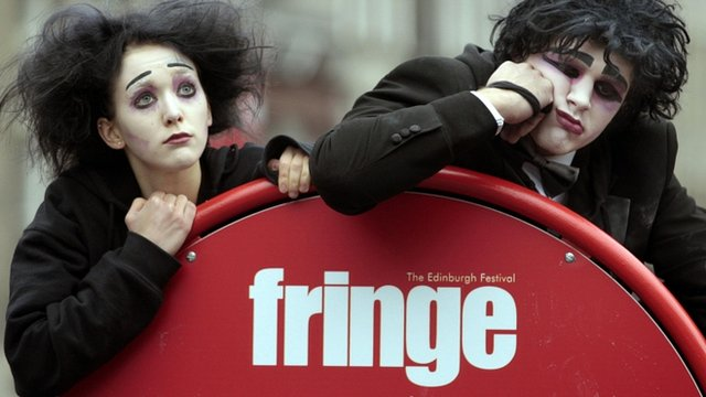 Actors pose by a sign for the Edinburgh Fringe Festival