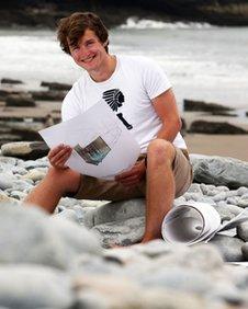 Joe Travers-Jones on beach with designs