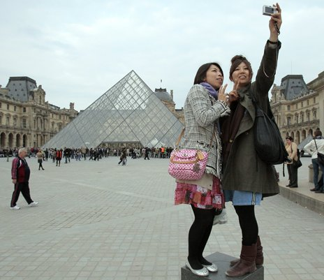 Tourists pose in front of the Louvre