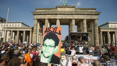 "A participant holds up a picture of former Edward Snowden with the word ""asylum"" written above it at a protest gathering in front of the Brandenburg Gate on July 27, 2013 in Berlin, Germany"