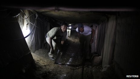 Palestinian tunnel workers inside a smuggling tunnel under the Gaza-Egypt border on 19 July 2013