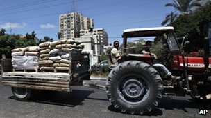 Palestinian workers ride a tractor carrying cement bags in GAza on 31 July 2013