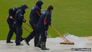 Ground staff clear rain off the covers