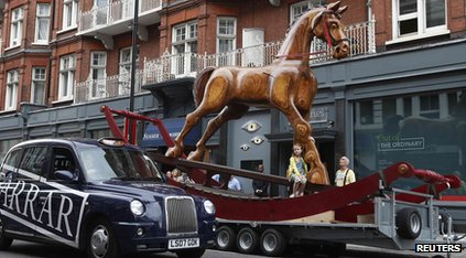 A girl poses on a giant two-storey rocking horse outside Christie's auction house in London