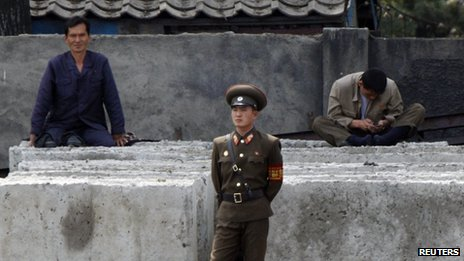 A North Korean worker checks his mobile phone as a soldier stands in front along the banks of Yalu River, near the North Korean town of Sinuiju, opposite the Chinese border city of Dandong, 7 June2013.
