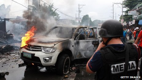 Emergency teams attend the scene following a powerful car bomb explosion in the southern Philippine city of Cotabato on 5 August 2013