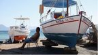 Man relaxing near boats on a Greek island