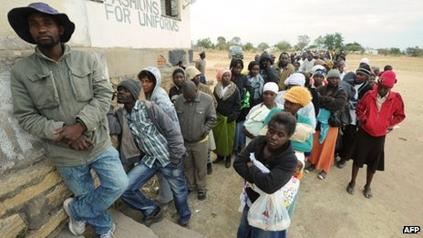 Zimbabweans wait in line as they prepare to cast their ballots at a polling station 60km north of Harare