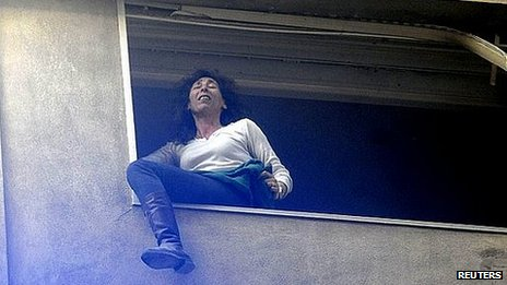 Woman waits on window ledge to be rescued. 6 Aug 2013