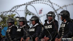 Thai riot policemen stand guard behind a barricade outside Government House in preparation for anti-government protests on 7 August 2013