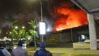 People watch a large blaze raging at the Jomo Kenyatta International Airport in Nairobi, Kenya, early Wednesday 7 Aug 2013.