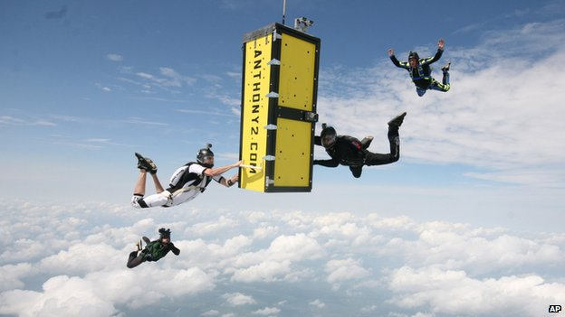 A yellow box falls through the clouds surrounded by skydivers in black costume.