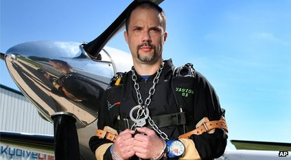 Anthony Martin stands in front of a plane with his hands chained together