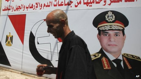 Salah Abdel Moneim, 40, an anti-Morsi supporter of Egypt's army walks in front of his shop, with huge posters of Egypt's army chief General Abdel Fattah al-Sisi in downtown Cairo, 7 August, 2013.