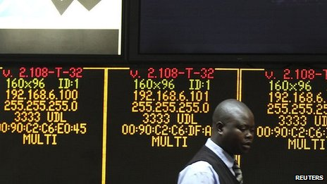 A man walks past an electronic display screen at the close of trading in Harare